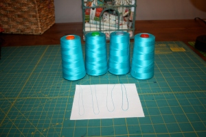 Four cones of Aurifil thread in various weights.