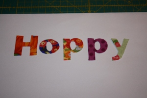 Applique letters after cutting out.